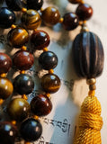 Close up view of dark brown barrel-shaped wood guru. Goldenrod tassel. Red, Blue, and Gold Tiger Eye beads.