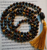 full view of knotted mala. Red Tiger Eye. Gold Tiger Eye. Blue Tiger Eye. Goldenrod tassel. Carved dark brown wood guru.