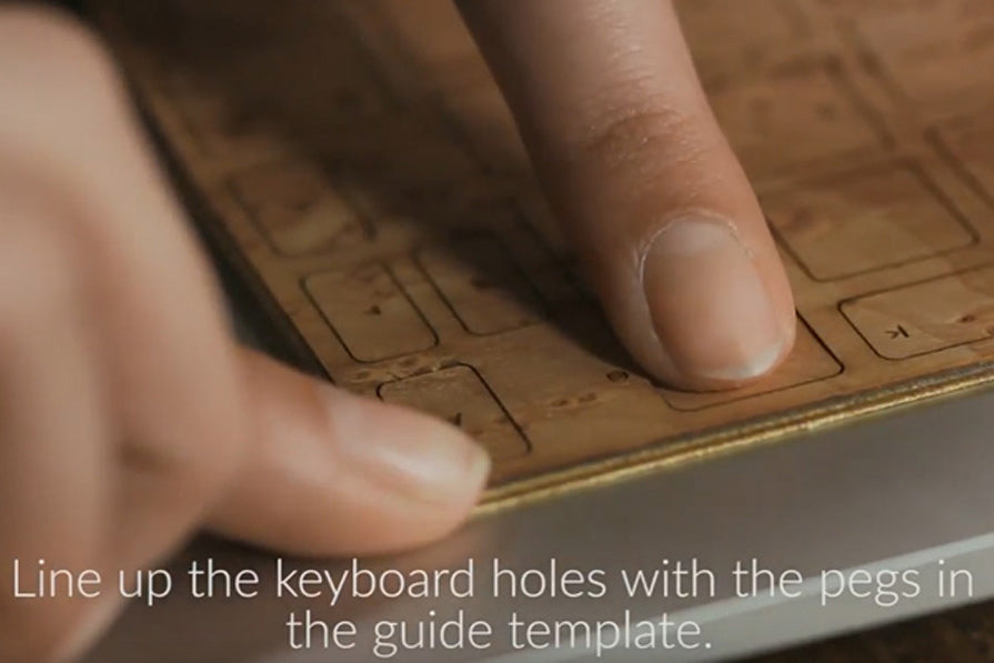 Line up the keyboard holes with the pegs on the guide