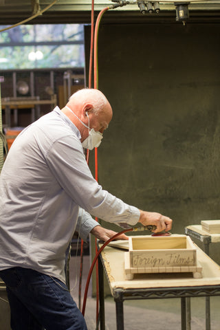 Artisan sanding and smoothing a memory box after burning/etching process.