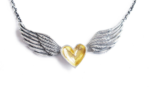 A handmade necklace featuring a silver and gold heart centred between sterling silver wings on a sterling silver chain. The silver wings have been darkened with a black patina to accent the handmade details.