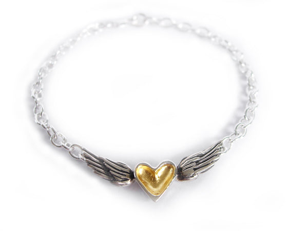 A handmade sterling silver bracelet featuring a black patina heart centered between silver wings on a silver chain