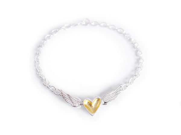 A handmade sterling silver bracelet featuring a 23k gold leafed heart centered between silver wings on a silver chain.