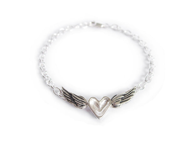 A handmade sterling silver bracelet featuring a silver heart centered between wings on a silver chain.