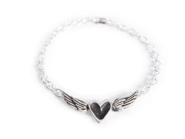 A handmade sterling silver bracelet featuring a black patina heart centered between silver wings on a silver chain.