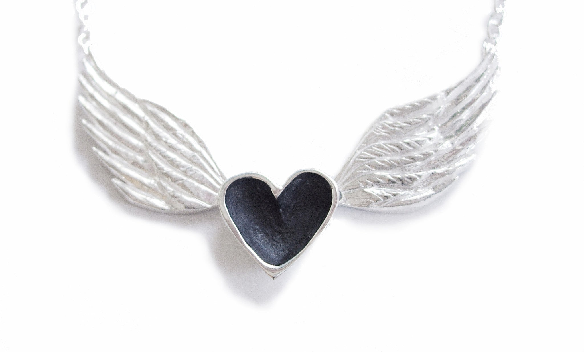 A handmade necklace featuring a silver heart with black patina centered between sterling silver wings on a sterling silver chain.