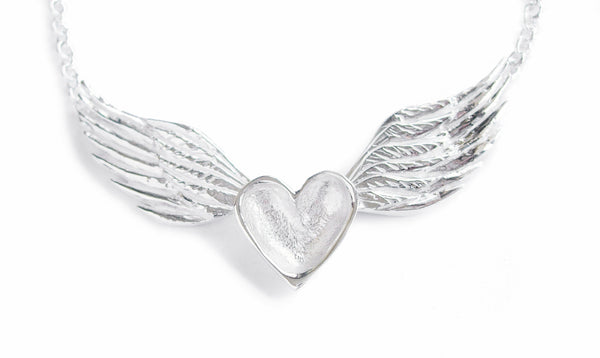 A handmade necklace featuring a sterling silver heart centered between silver wings on a sterling silver chain.
