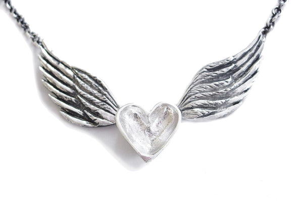 A handmade necklace featuring a sterling silver heart centered between silver and patina darkened wings on a sterling silver chain.