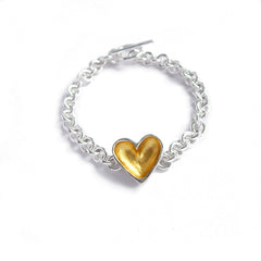 A handmade bracelet featuring a sterling silver heart with a gold centre and silver chain.