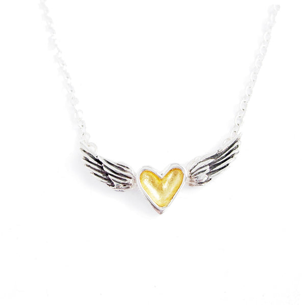 A handmade necklace featuring a small gold and silver heart centered between sterling silver wings on a sterling silver chain. The wings are darkened with a black patina to highlight the handmade details.