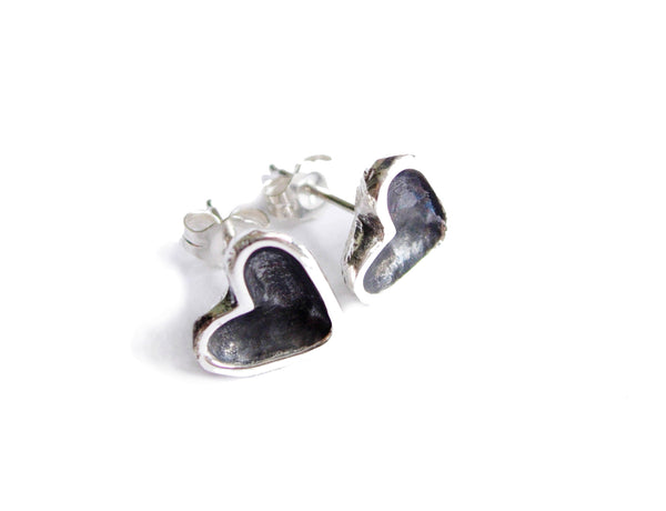 Tiny sterling silver heart stud earrings with a black patina centre.