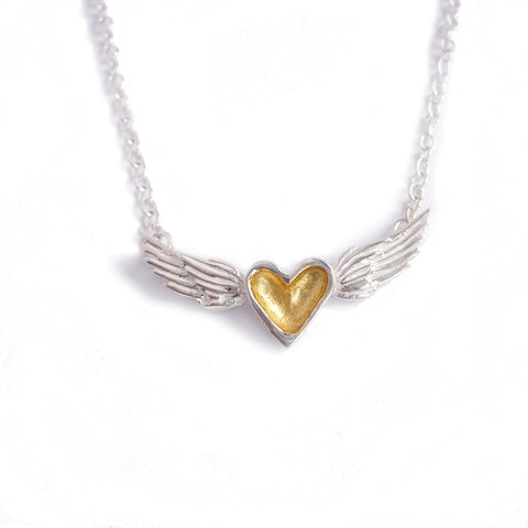A handmade necklace featuring a gold and silver heart centered between sterling silver wings on a sterling silver chain.