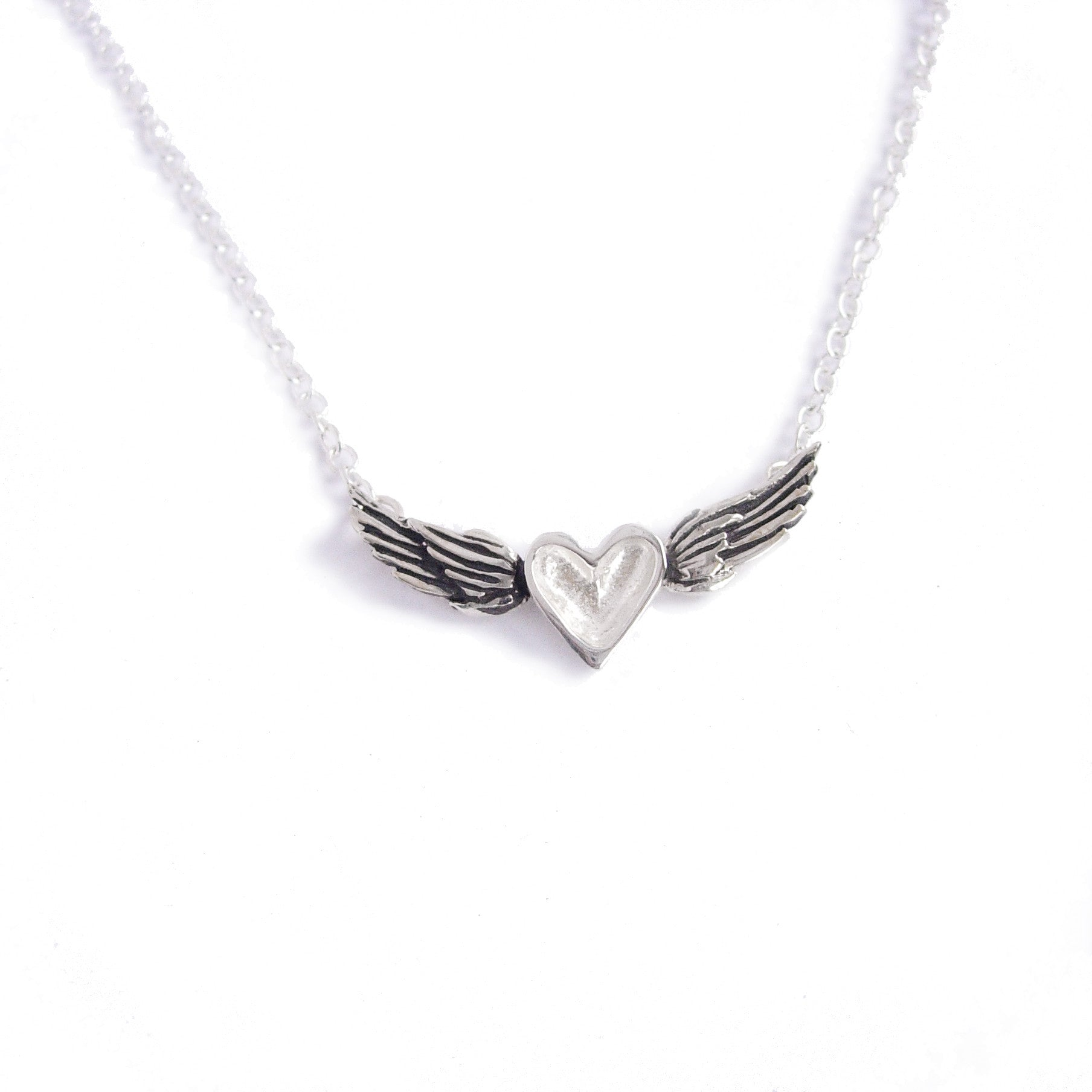 A handmade necklace featuring a sterling silver heart centered between blackened sterling silver wings on a silver chain.