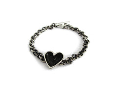A handmade bracelet featuring a sterling silver heart with a dark patina centre on a darkened silver chain.