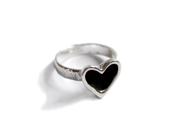 A silver and patina darkened open heart ring