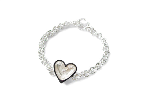 A handmade bracelet featuring a sterling silver heart and silver chain.