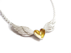 A handmade necklace featuring a silver and gold heart centered between sterling silver wings on a sterling silver chain.