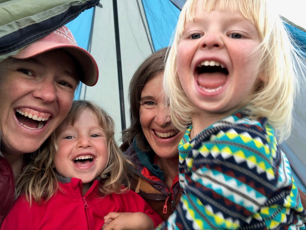 Family photo of Jen, her wife Liz, and their two young children, on a camping trip.