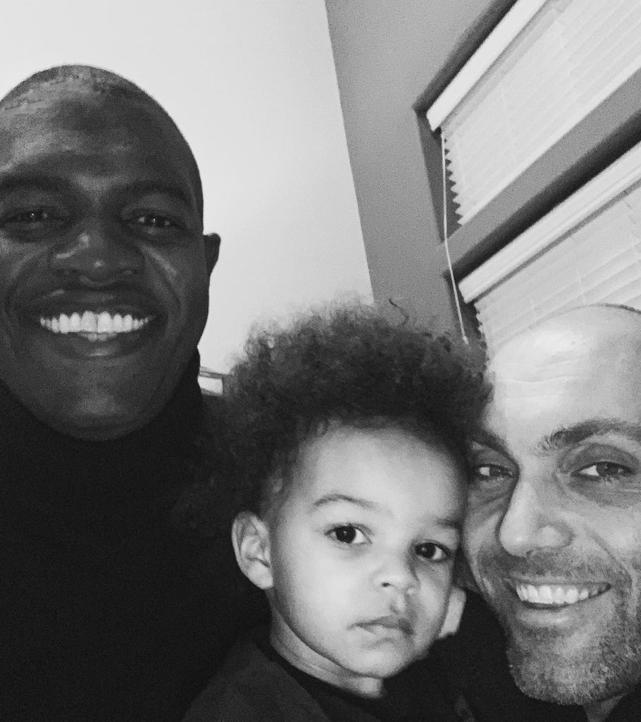 Black and white photo of smiling fathers, Kwesi and Jackson, with their young son, taking a selfie at home.