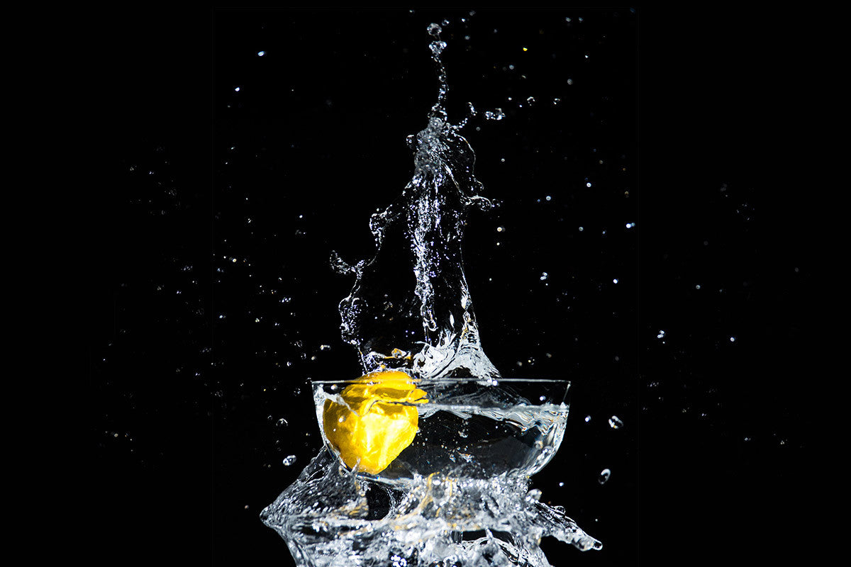 Lemon dropping into a glass of water