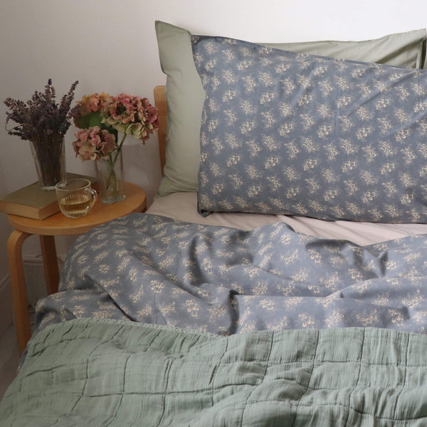 Square quilted blanket in sage 100% soft cotton gauze and lightly filled with anti-allergy polyester comes in 4 different sizes and can be mixed with our beautiful Celia print bedding in soft blue and stone by camomile london