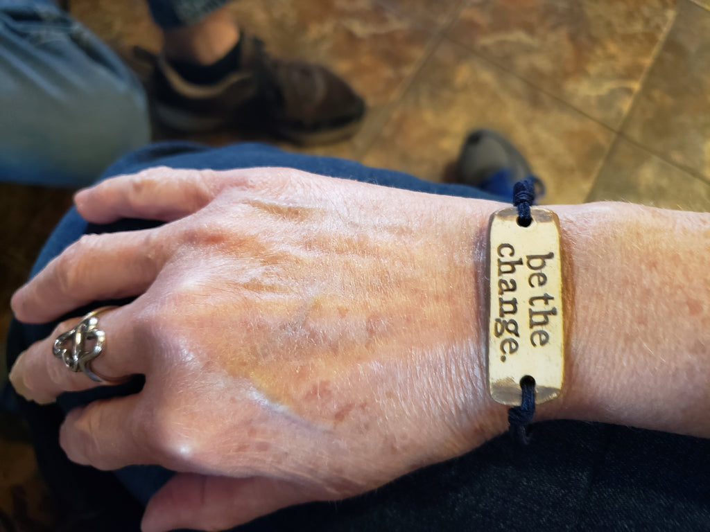 """Image depicts a """"be the change"""" bracelet on a woman's wrist."""