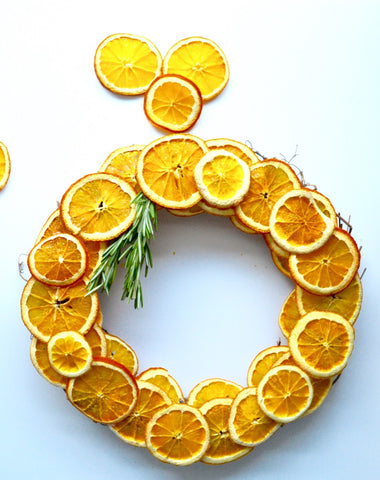 Wreath made of sliced dried citrus rounds with a sprig of rosemary