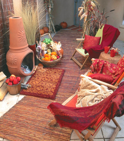 Cozy courtyard decorated for autumn with chairs around a fireplace