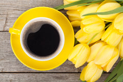 Yellow tulips next to yellow coffee cup on a wood surface
