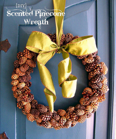 pine cone wreath with yellow silk ribon hanging on blue door