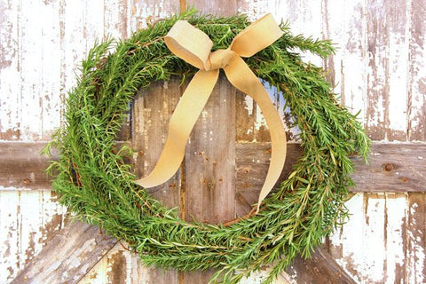 Rosemary wreath with gold ribbon on rustic door