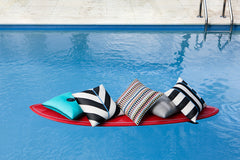 Elaine Smith Outdoor Pillows on surf board in a pool