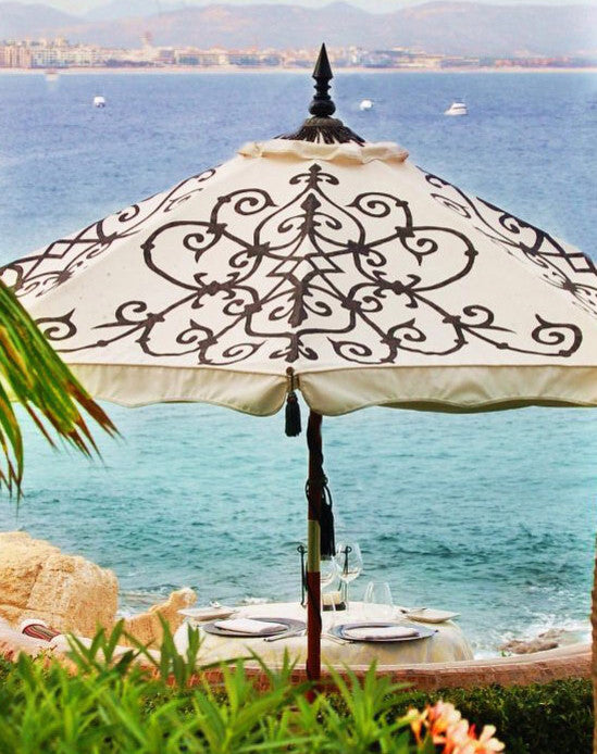 Alura hand-painted patio umbrellaover dining table with coastal view