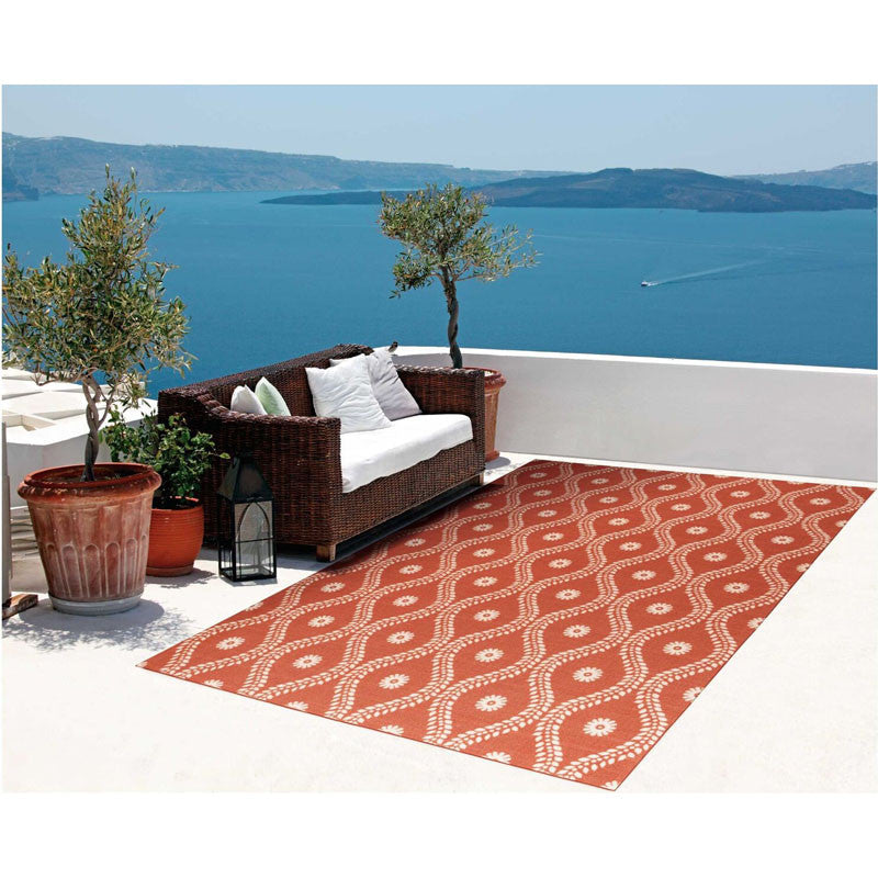 Alana Outdoor Rug in Rust on a seaside patio