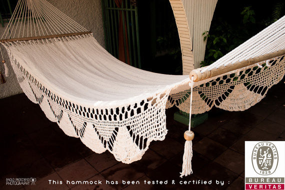 Detail of hand-made woven hammock with bars and fringe in cream