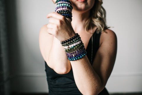 woman with stacks of colorful gemstone bracelets