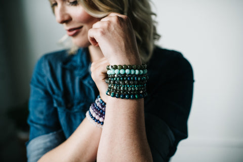 blonde model wearing stack of colorful crystal bracelets