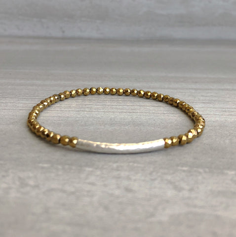 Gold beaded bracelet with silver bar accent