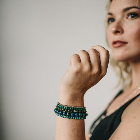 Woman wearing blue and green gemstone bracelets