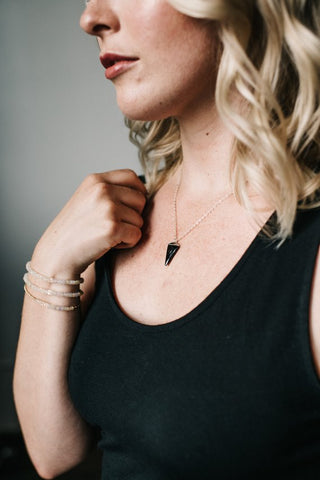 Woman wearing black triangle necklace