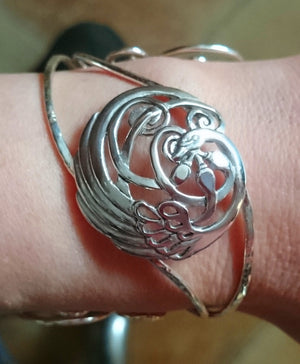 Wear the Sterling Sliver Children of Lir Four Swan Bangle with medalion and tri-spiral. Cuff is handmade in Ireland.
