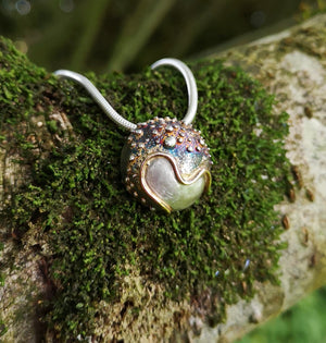The Small Cúrsa an tSaoil Pendant hand made by Elena Brennan Jewellery on the branch of a tree.