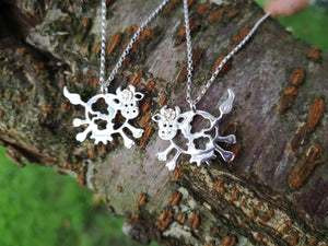 Daisy the Cow Pendant hanging on an 18 inch chain, handmade from sterling silver and complete with a 14ct gold flower.