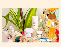 Skincare products spread out on a countertop, with a plant in the background