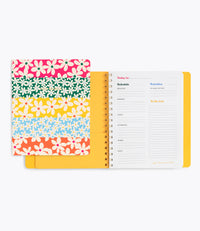 Front cover with rainbow striped daisies on top of an open to do planner