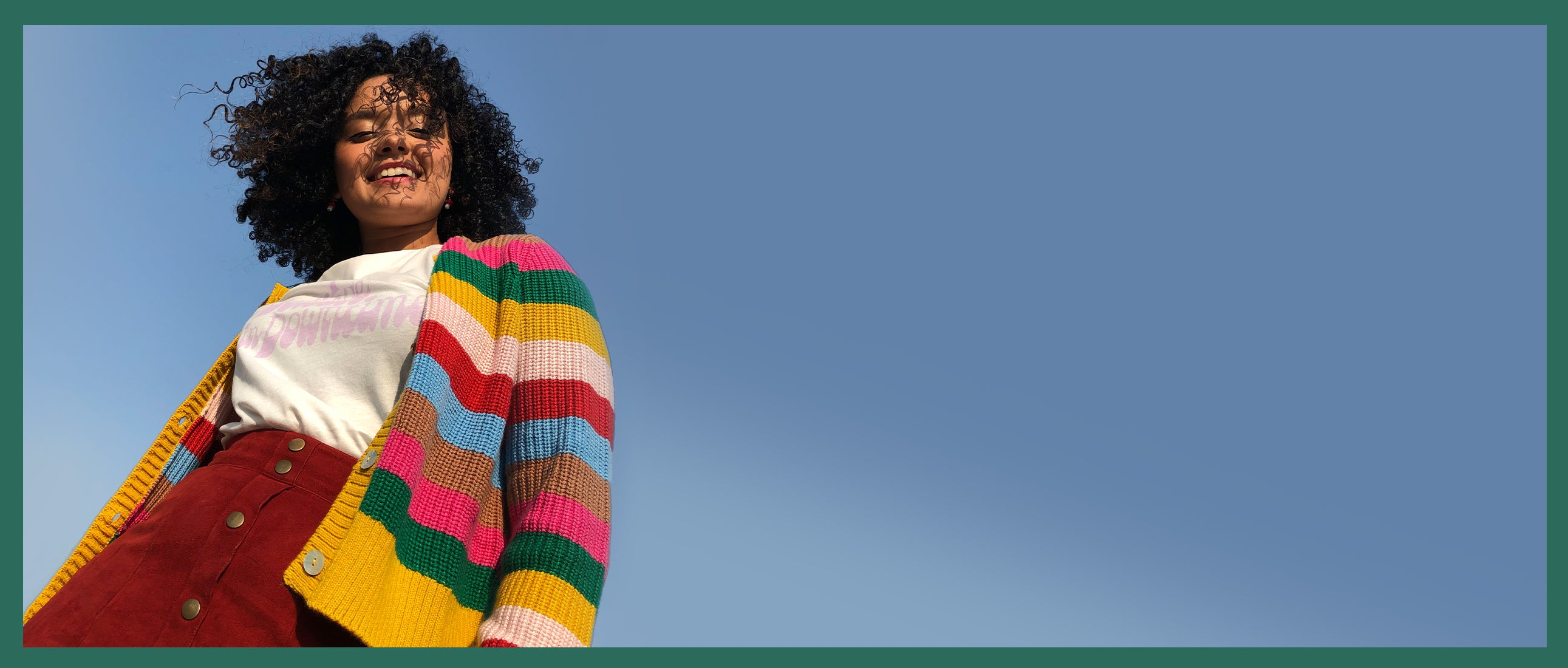 Model wearing yellow, green, pink, brown, blue and red striped cardigan
