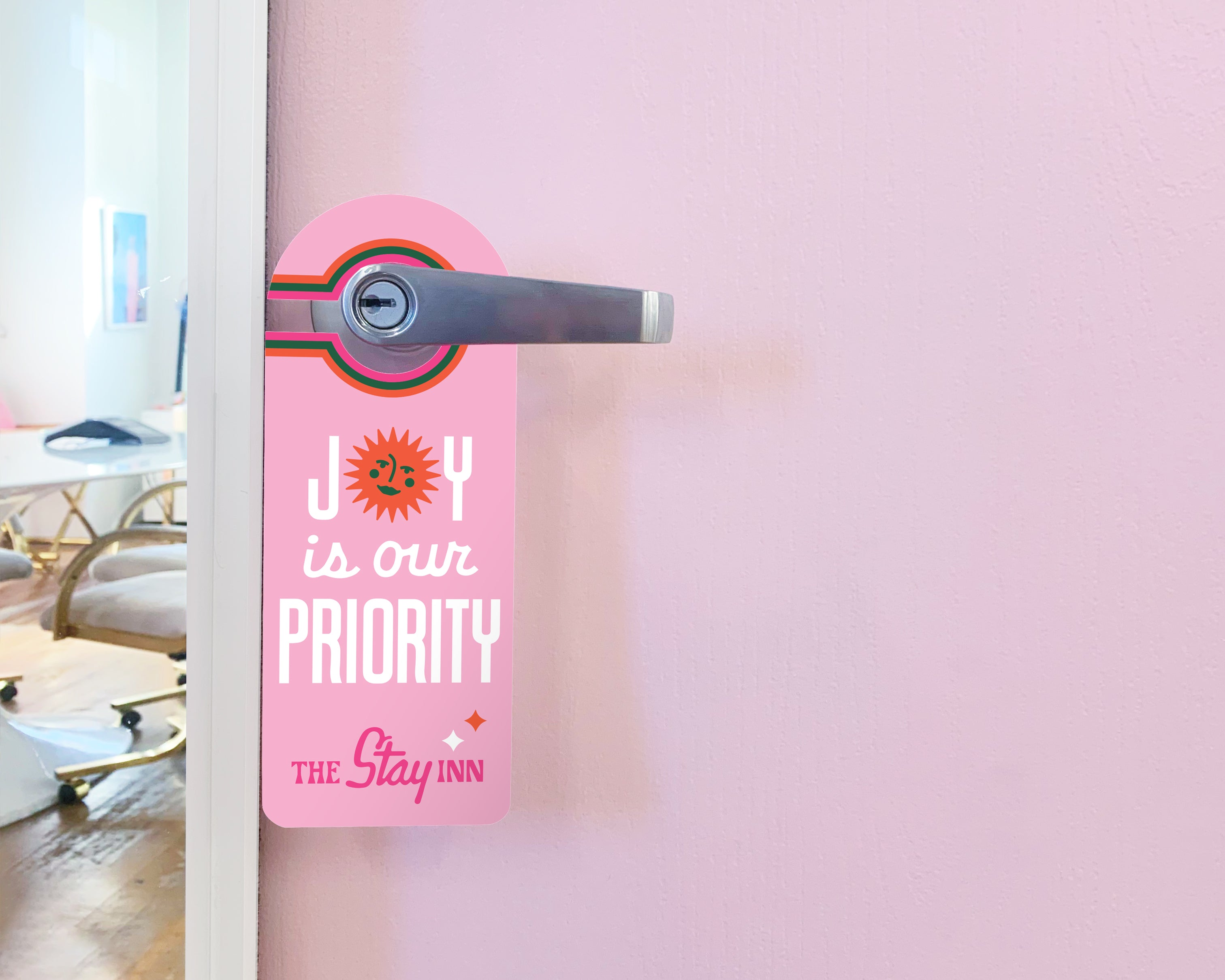 Door hanger that says Joy is our Priority on a purple door