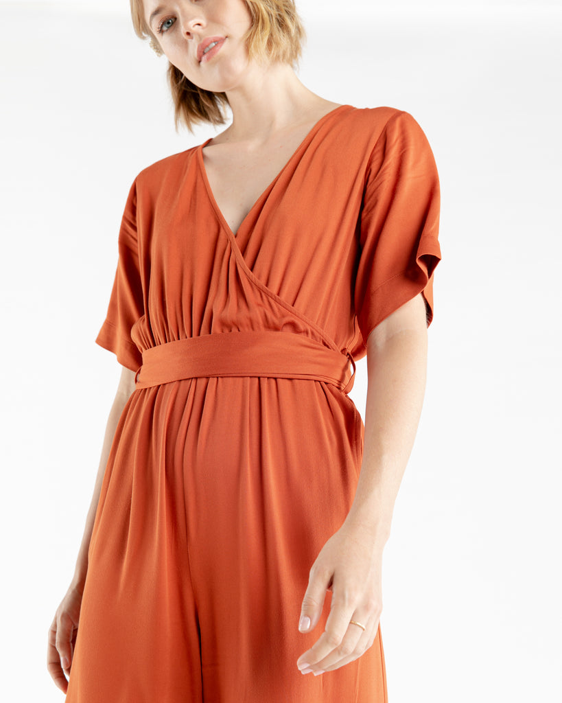 Rust color jumpsuit with a tie belt.