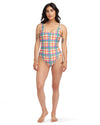 Model wearing yellow, blue, green, and red plaid scoop-neck one-piece swimsuit