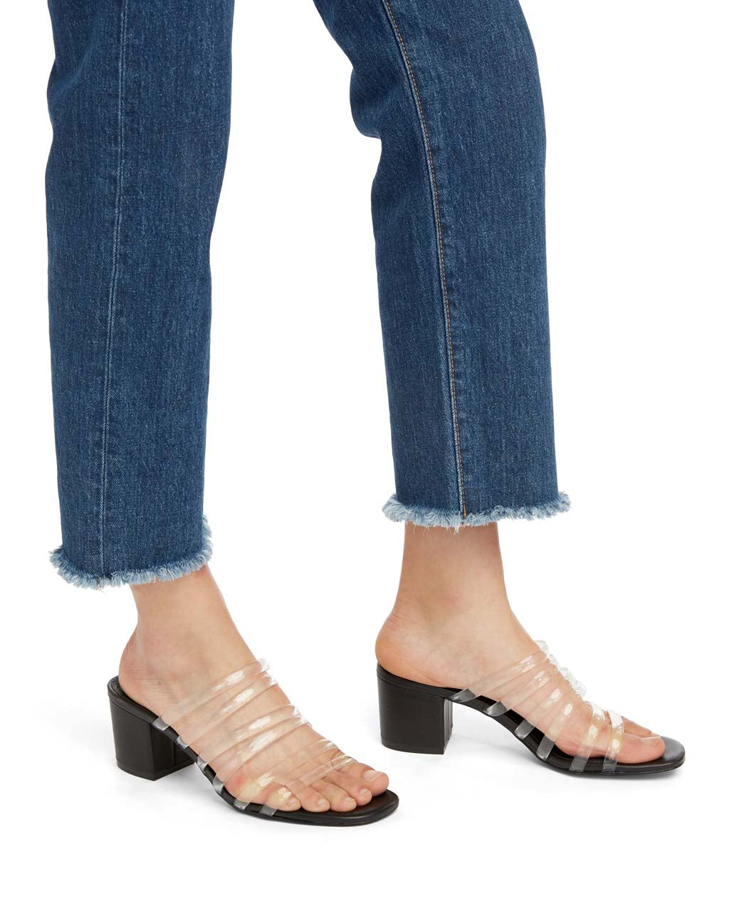 closeup of the legs of a women wearing jeans and clear strappy heels